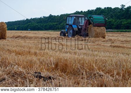 A Tractor With A Trailed Bale Making Machine Collects Straw Rolls In The Field And Makes Round Large