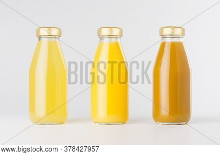 Orange, Yellow Fruit Juices Collection In Glass Bottles With Cap In Row Mock Up On White Background,