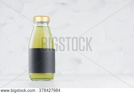Green Kiwi Juice In Glass Bottle With Gold Cap And Black Blank Label Mock Up On White Wood Table In