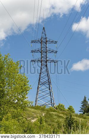 High Voltage Pillar For High Voltage Transmission. The High-voltage Support Stands On A Hill.