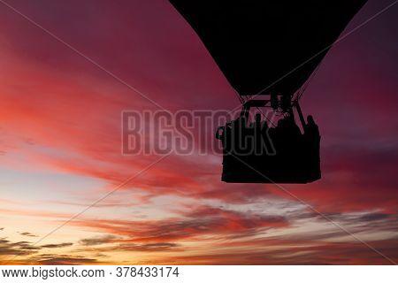 Hot Air Balloon Flying At Sunset Sky.