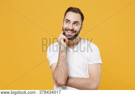 Pensive Young Bearded Man Guy In White Casual T-shirt Posing Isolated On Yellow Background Studio Po