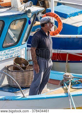Heraklion, Greece - November 12, 2019: A Unidentified Boatman Standing In A Wooden Fishing Boat In P