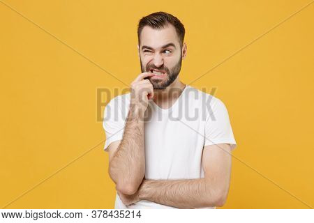 Preoccupied Worried Young Bearded Man Guy In White Casual T-shirt Posing Isolated On Yellow Wall Bac