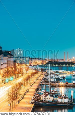 Helsinki, Finland. View Of Pohjoisranta Street And Ships, Boats And Yachts Moored Near Pier In Eveni