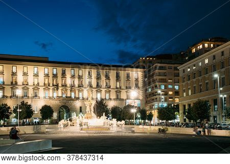 Naples, Italy. Fountain Of Neptune On Piazza Municipio In Evening Or Night Illuminations.