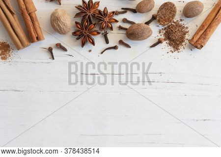 Mix of spices, cinnamon, nutmeg, star anise and cloves on textured white timber.  Flat lay, top view, with copy space. Christmas holiday spices.
