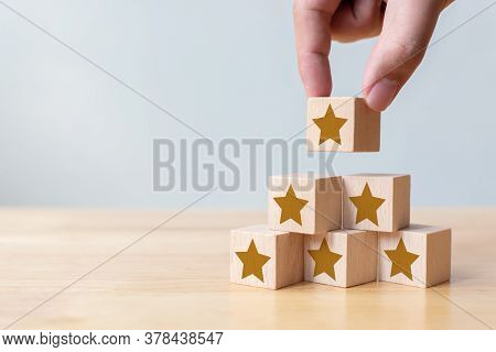 Hand Arranging Wood Block Stacking As Step Stair With Five Star Shape. The Best Excellent Business S