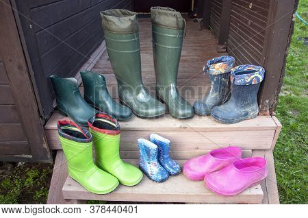 Old Dirty Rubber Boots Of A Big Family Stand On The Wooden Floor Of A Country House Porch Lit By Sum