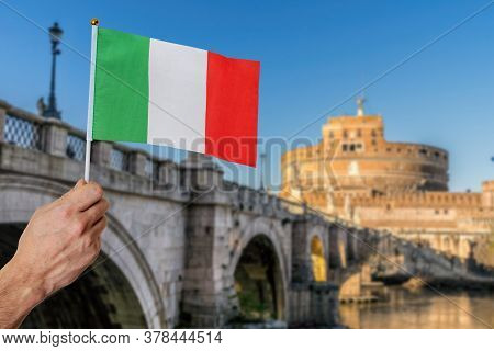 Man Is Holding Italian Flag In Hand. Saint Angel Castle In Background.