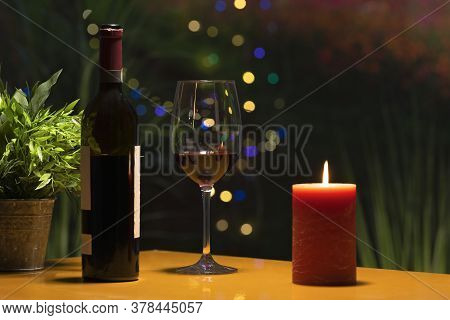 Close Up Of A Glass Of Wine Surrounded By A Wine Bottle And A Lit Candle On A Table On An Out Of Foc
