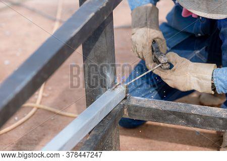 Man Welds A Metal With A Welding Machine, Profession Of Welder. Arc Welding Of A Steel In Constructi