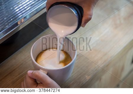 Barista In Cafe Or Coffee Bar Preparing Proper Cappuccino Pouring Milk Froth In A Cup. Waiter Hands