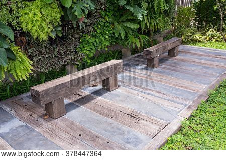 Old Wooden Chair In Garden. Wood Bench Made From Log. Bench Made Of A Single Piece Of Wood On A Meta