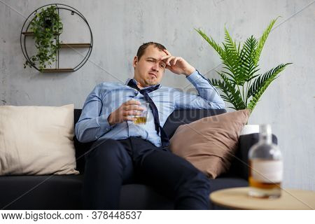 Alcoholism, Business And Stress Concept - Drunk Businessman Drinking Alcohol At Home Or Office