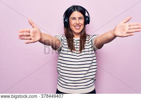 Young beautiful brunette woman listening to music using headphones over pink background looking at the camera smiling with open arms for hug. Cheerful expression embracing happiness.