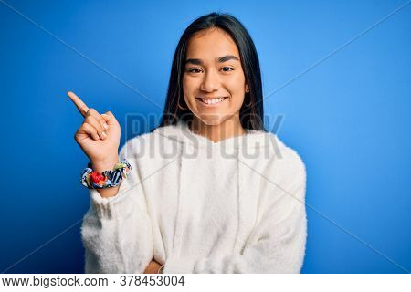 Young beautiful asian sportswoman wearing sweatshirt standing over isolated blue background with a big smile on face, pointing with hand and finger to the side looking at the camera.
