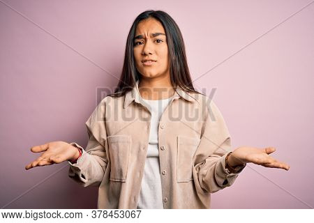 Young beautiful asian woman wearing casual shirt standing over pink background clueless and confused with open arms, no idea concept.