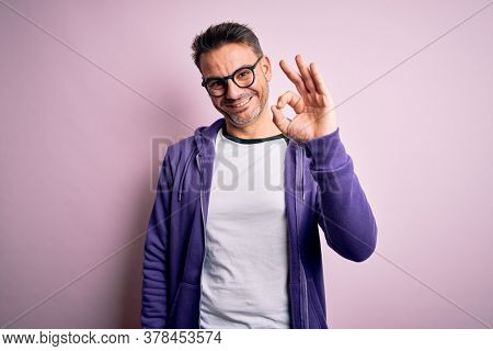 Young handsome man wearing purple sweatshirt and glasses standing over pink background smiling positive doing ok sign with hand and fingers. Successful expression.