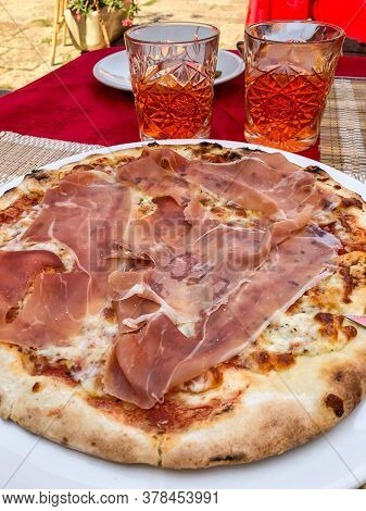 Pizza With Prosciutto And Glasses Of Aperol Spritz