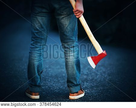 A Determined Man In Blue Jeans, Who Is Holding A Long Axe With A Red Sharp Blade, Stands On An Aspha