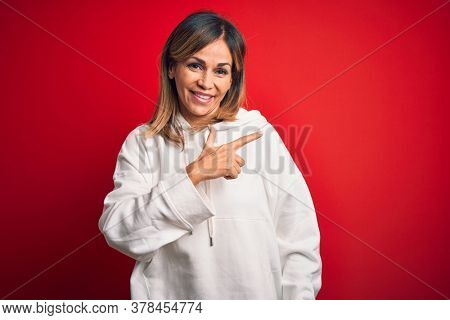 Middle age beautiful sportswoman wearing casual sweatshirt over isolated red background cheerful with a smile on face pointing with hand and finger up to the side with happy and natural expression