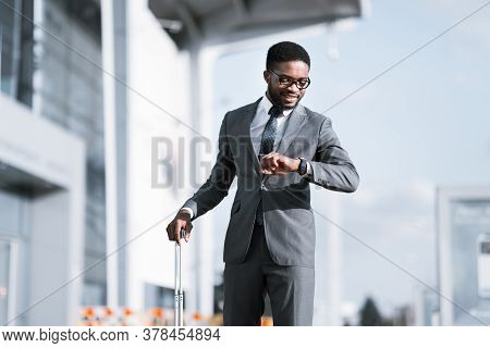 Punctual African American Businessman Smiling Looking At Wristwatch Arriving At Airport Just In Time