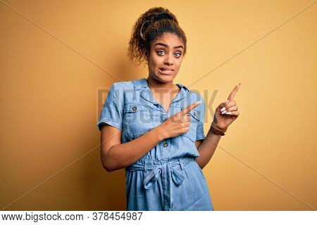 Young beautiful african american girl wearing denim dress standing over yellow background Pointing aside worried and nervous with both hands, concerned and surprised expression