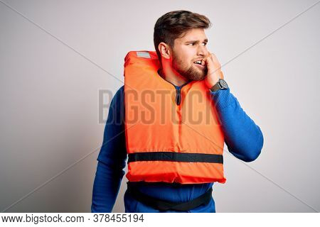 Young blond tourist man with beard and blue eyes wearing lifejacket over white background looking stressed and nervous with hands on mouth biting nails. Anxiety problem.