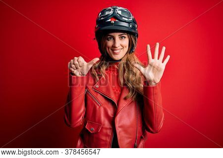 Young beautiful brunette motrocyclist woman wearing moto helmet over red background showing and pointing up with fingers number six while smiling confident and happy.