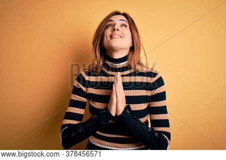 Young beautiful brunette woman wearing striped turtleneck sweater over yellow background begging and praying with hands together with hope expression on face very emotional and worried. Begging.