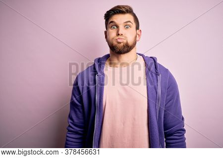 Young blond man with beard and blue eyes wearing purple sweatshirt over pink background puffing cheeks with funny face. Mouth inflated with air, crazy expression.