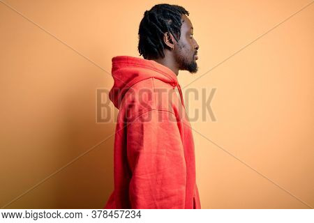 Young african american sporty man wearing sweatshirt with hoodie over yellow background looking to side, relax profile pose with natural face with confident smile.