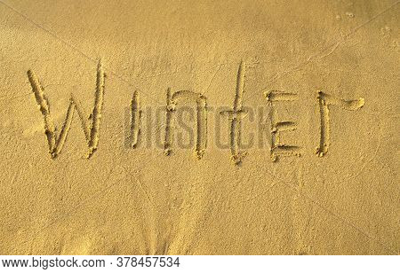 Winter Word On Beach Sand. Winter Printed On A Yellow Sand, Top View.