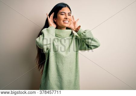 Young beautiful hispanic woman wearing green winter sweater over isolated background Trying to hear both hands on ear gesture, curious for gossip. Hearing problem, deaf