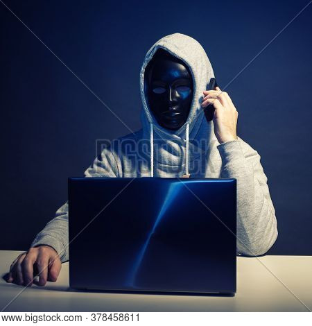 Anonymous Hacker In Mask Programmer Uses A Laptop And Talking On The Phone To Hack The System In The