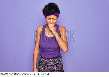 Beautiful african american afro woman wearing casual sportswear over purple background feeling unwell and coughing as symptom for cold or bronchitis. Health care concept.