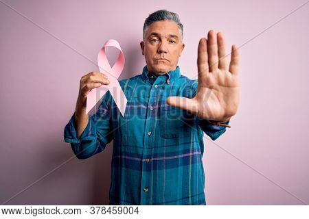 Middle age handsome grey-haired man holding pink cancer ribbon over isolated background with open hand doing stop sign with serious and confident expression, defense gesture
