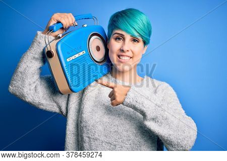 Young woman with blue fashion hair listening to music holding vintage portable radio very happy pointing with hand and finger