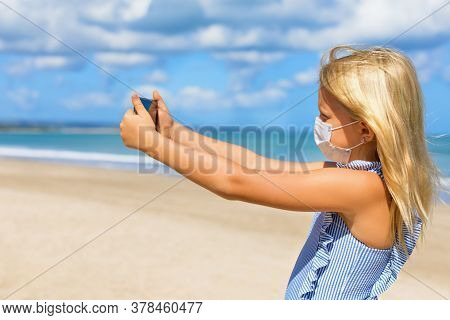 Funny Girl Taking Selfie Photo By Smartphone On Tropical Sea Beach. New Rules To Wear Cloth Face Cov