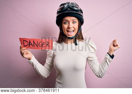 Beautiful motorcyclist woman with blue eyes wearing moto helmet holding danger message screaming proud and celebrating victory and success very excited, cheering emotion