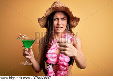 Beautiful woman with blue eyes on vacation wearing bikini and hawaiian lei drinking cocktail annoyed and frustrated shouting with anger, crazy and yelling with raised hand, anger concept