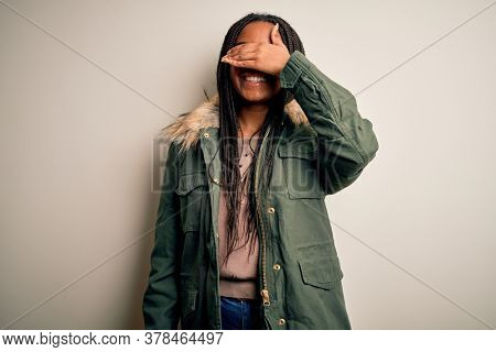 Young african american woman wearing winter parka coat over isolated background smiling and laughing with hand on face covering eyes for surprise. Blind concept.