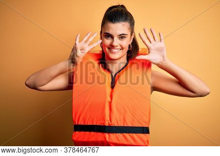 Young beautiful brunette woman wearing orange safe lifejacket over yellow background showing and pointing up with fingers number nine while smiling confident and happy.