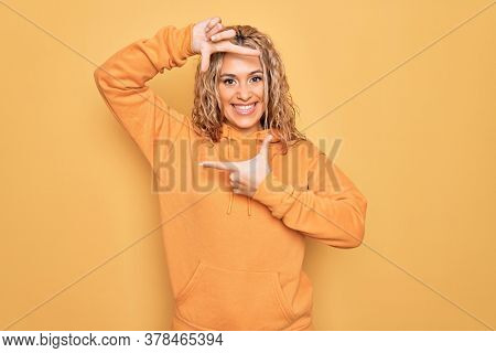 Young beautiful blonde sporty woman wearing casual sweatshirt over yellow background smiling making frame with hands and fingers with happy face. Creativity and photography concept.