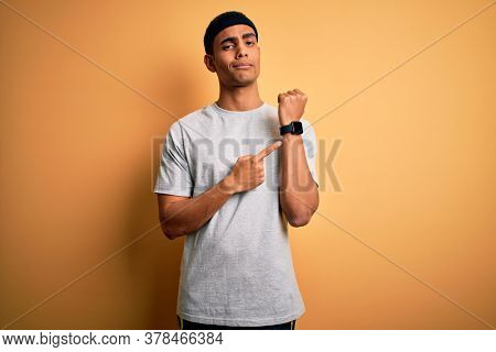 Handsome african american sportsman doing sport wearing sportswear over yellow background In hurry pointing to watch time, impatience, looking at the camera with relaxed expression