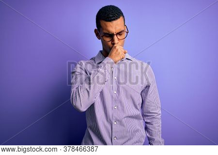 Handsome african american man wearing striped shirt and glasses over purple background feeling unwell and coughing as symptom for cold or bronchitis. Health care concept.