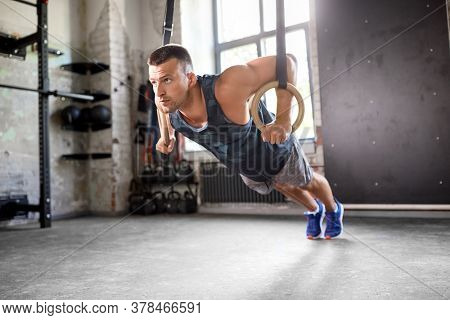 fitness, sport, bodybuilding and people concept - young man doing push-ups on gymnastic rings in gym