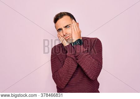 Young handsome man with blue eyes wearing casual sweater standing over pink background Tired hands covering face, depression and sadness, upset and irritated for problem
