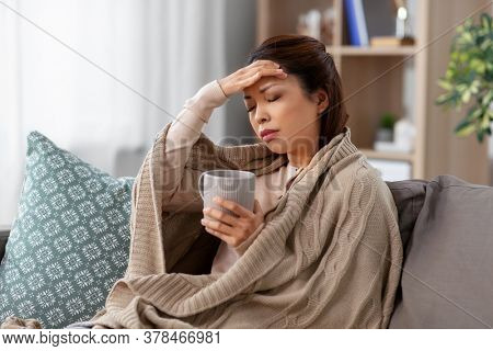 health, cold and people concept - sad sick young asian woman in blanket drinking hot tea at home